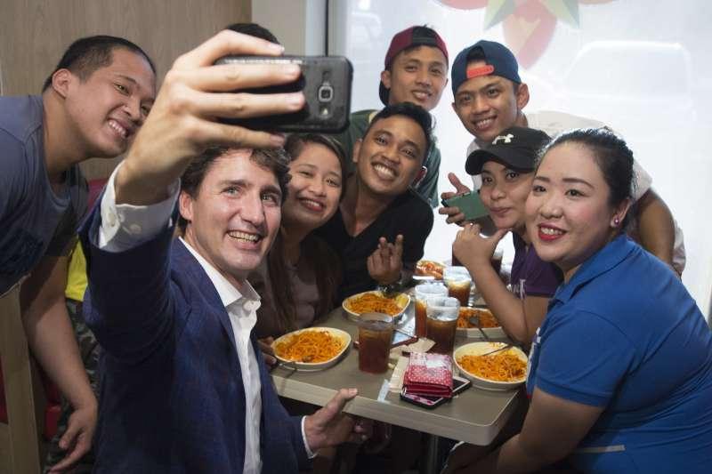 加拿大總理杜魯道突然現身菲律賓連鎖速食店Jollibee,與顧客自拍。(美聯社)