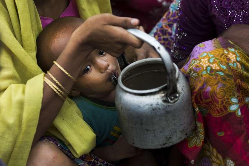 緬甸羅興亞難民小男孩,一邊喝媽媽餵的水,一邊靜靜的流淚。(AP)