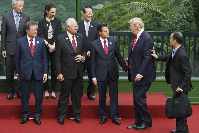 美國總統川普(右2)與紐西蘭總理雅頓(後排左2)出席APEC峰會(AP)