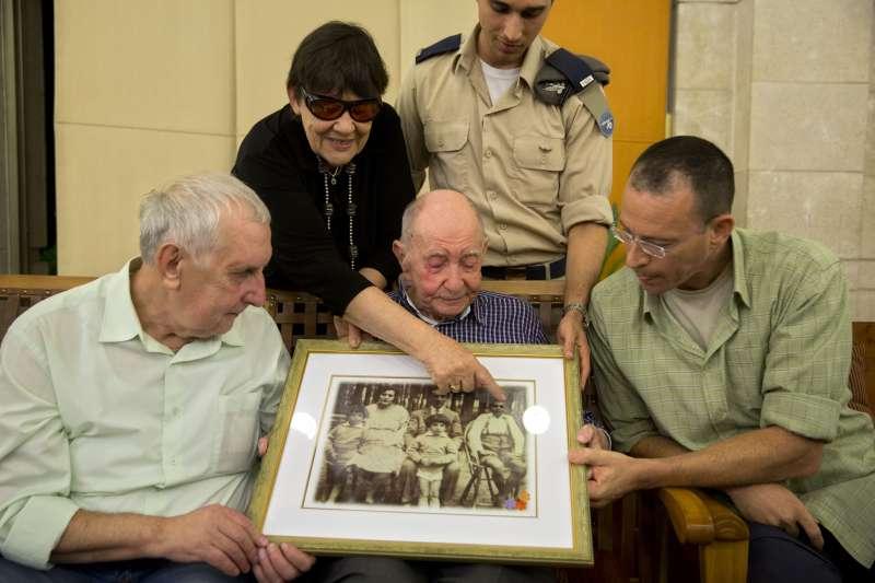 皮楚斯卡(中)與姪子亞利山卓(左)一起看著泛黃的家族照片(AP)