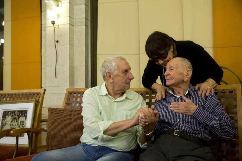 皮楚斯卡(右)與姪子亞利山卓(左)緊握著彼此的手聊天(AP)
