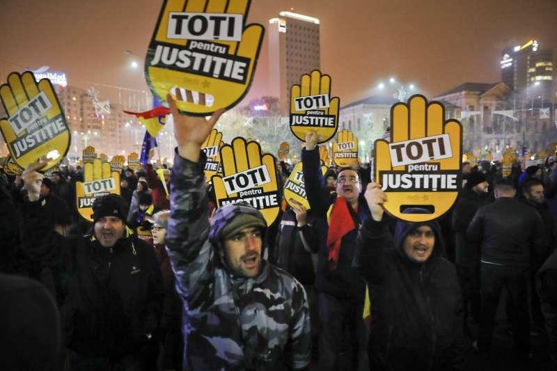 羅馬尼亞民眾高舉「為了正義」標語,抗議政府意圖為了私慾而修法。(美聯社)