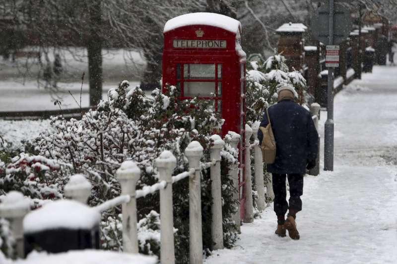 英國10日下大雪,白金漢郡馬洛鎮一名男子行經被雪覆蓋的電話亭(美聯社)