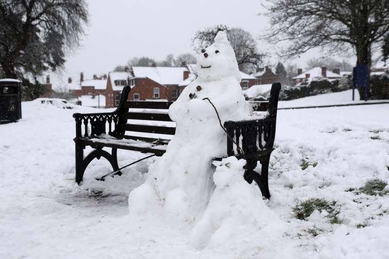 英國10日下大雪,英格蘭西密德蘭郡的伍斯特,有民眾在長凳上堆了雪人(AP)