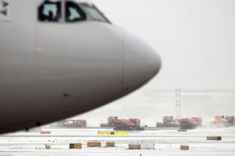 10日的大雪讓德國法蘭克福國際機場的航班大亂,鏟雪車忙著清除跑道上的積雪(AP)