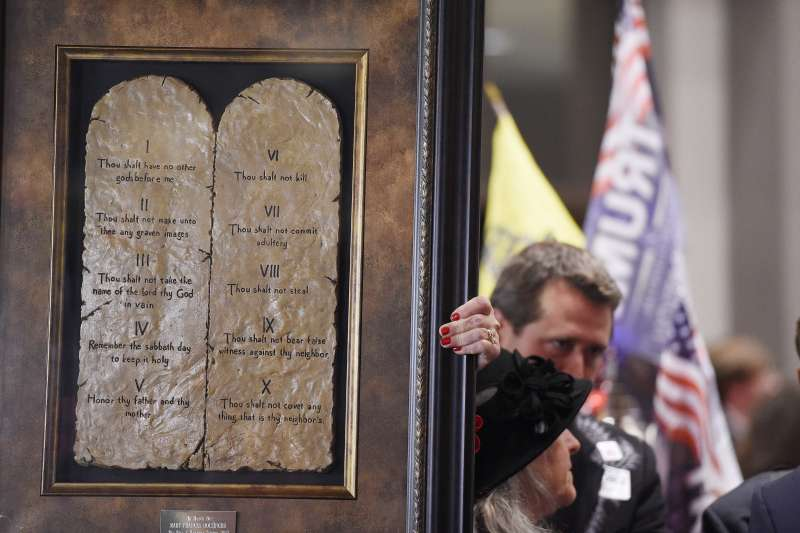 摩爾的支持者拿著「十誡」的照片,為摩爾打氣。(美聯社)
