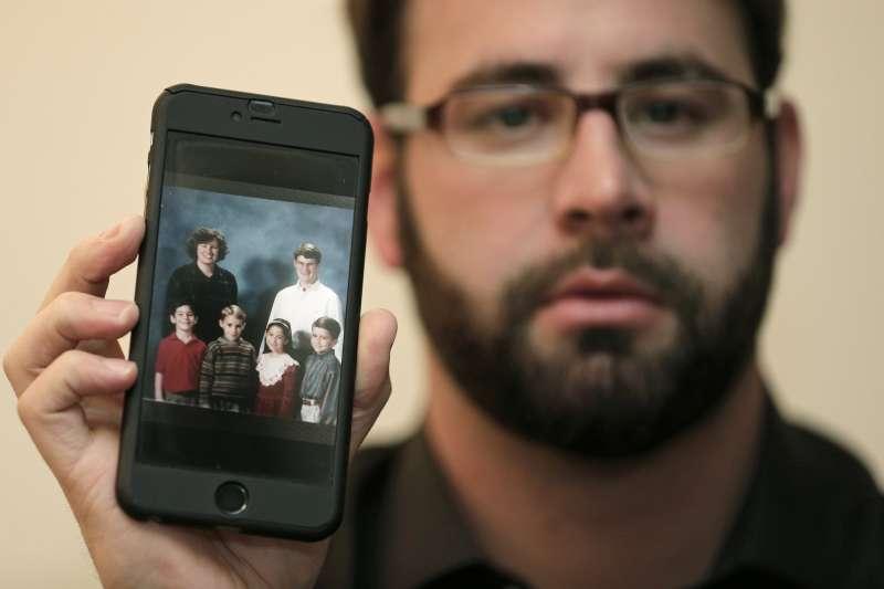 安德森(Jamey Anderson)向記者展示他的全家福。(美聯社)