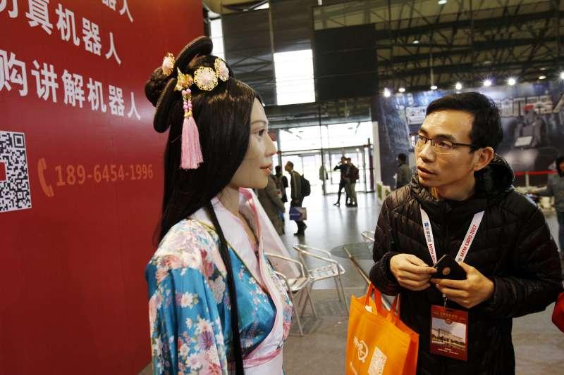 參觀者近距離觀察展會上一個古典造型的仿真機器人(新華社)