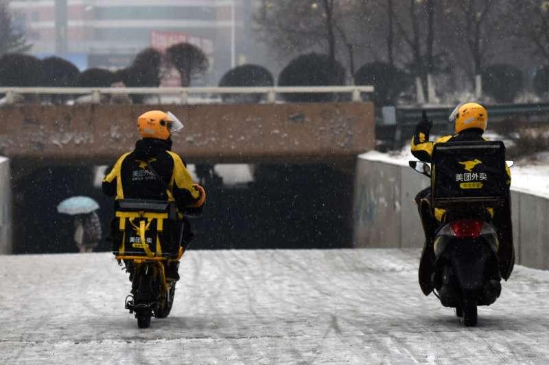 瀋陽街頭兩名送外賣的騎手冒雪前進(新華社)
