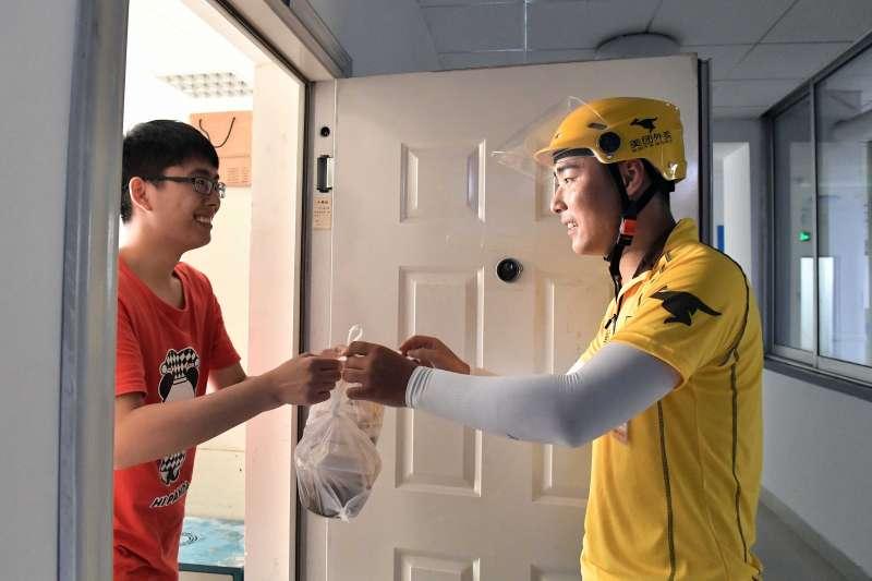 濟南一位送餐員將外賣送交訂餐客戶手中(新華社)