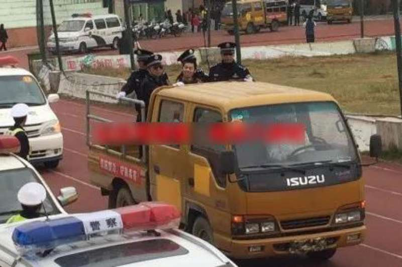 廣東汕尾、陸豐兩級法院聯合在陸豐東海鎮體育廣場召開宣判大會,被押送會場的犯人臉上露出詭異微笑。