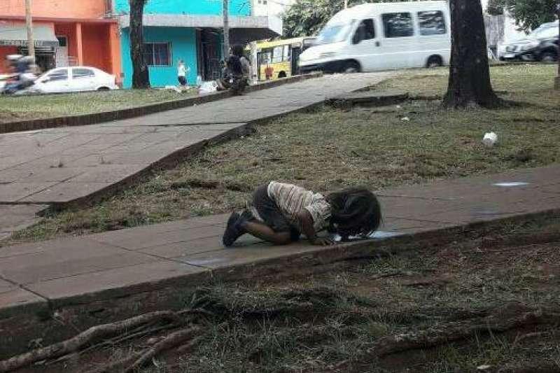 阿根廷東北部城市波沙達斯的街頭,一一個原住民小女孩,趴在地上一灘骯髒的積水前方舔舐。(Migue Ríos臉書)