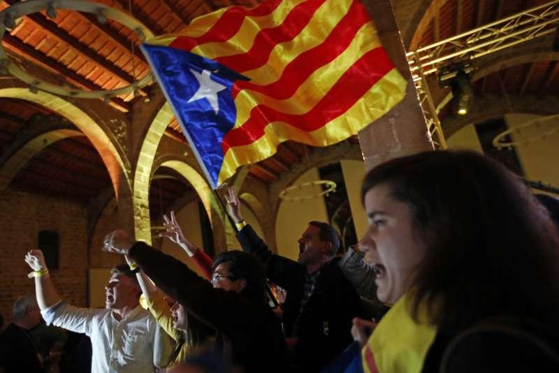 21日晚間,支持獨立的加泰隆尼亞巴塞隆納民眾揮舞象徵建國的「孤星旗」慶祝(AP)