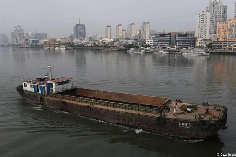 一艘北韓貨船行駛在鴨綠江上,對面就是中國城市丹東。(德國之聲)