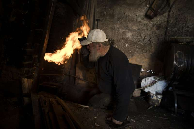 希臘陶藝師傅古馬斯正在試著控制窯內的溫度。(美聯社)