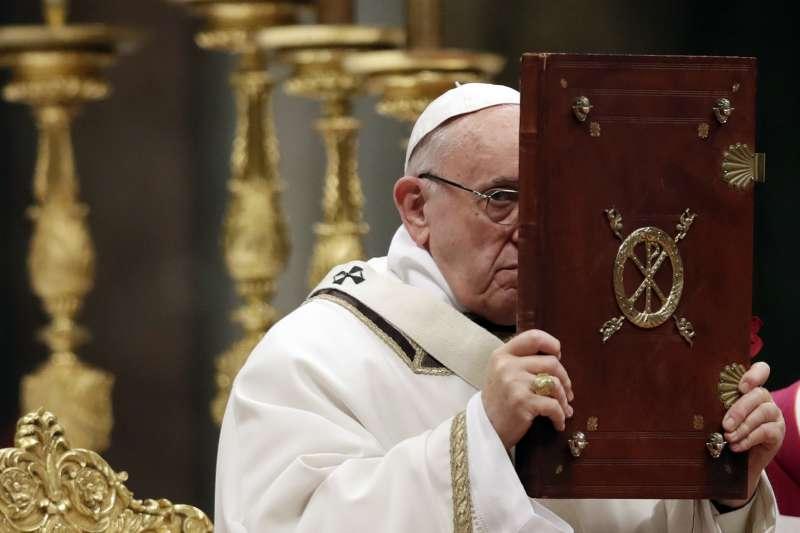 天主教教宗方濟各在耶誕子夜彌撒時,舉起《福音》(AP)