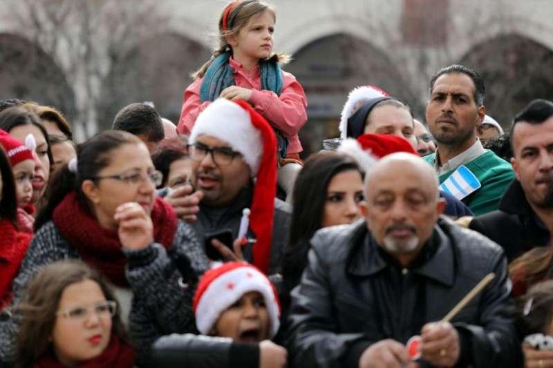 在伯利恆的聖誕教堂外面,人們舉行聖誕節慶祝活動。(美國之音)