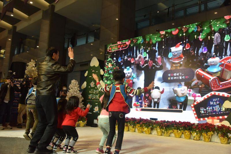 新北市長朱立倫開心地與小朋友們一起透過AR,蹦蹦跳跳的幫奇幻馬戲團桑塔熊修理燈泡。(圖/新北市政府提供)