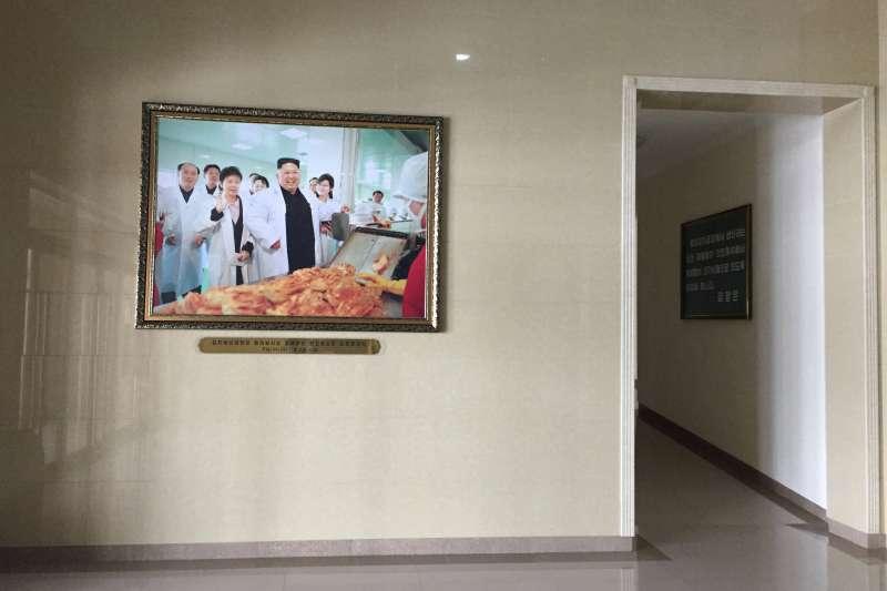 「柳京泡菜廠」中擺放著金正恩視察時的照片。(美聯社)