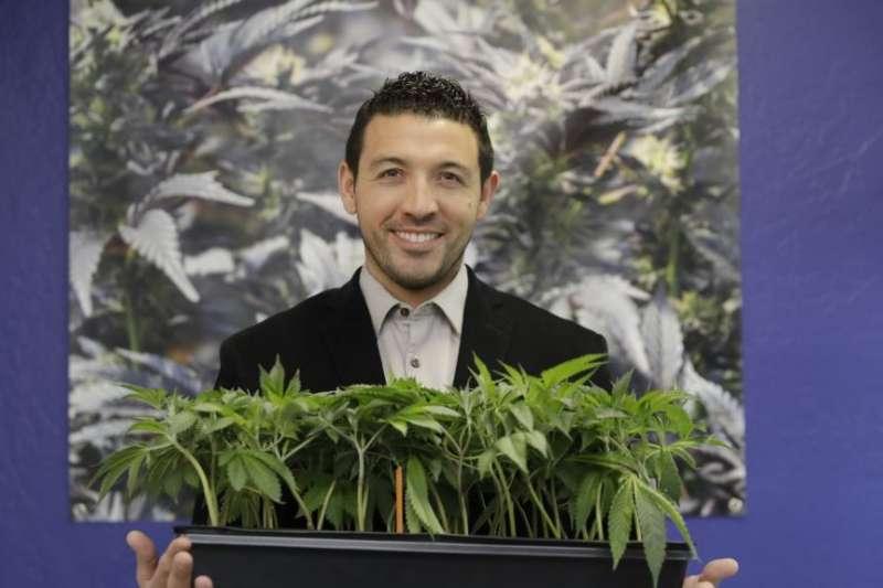 KindPeoples聯合創辦人和首席執行官哈利德·穆塔瓦基勒在他位於加州聖克魯茲的大麻藥店與幾株大麻合影。(美國之音)