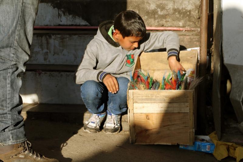 在街道上販售年節飾品的印度男孩,照片中是被稱為「曲瑪」,染成五種顏色的小麥束,通常插在盛裝糌粑的碗裡裝飾佛堂。