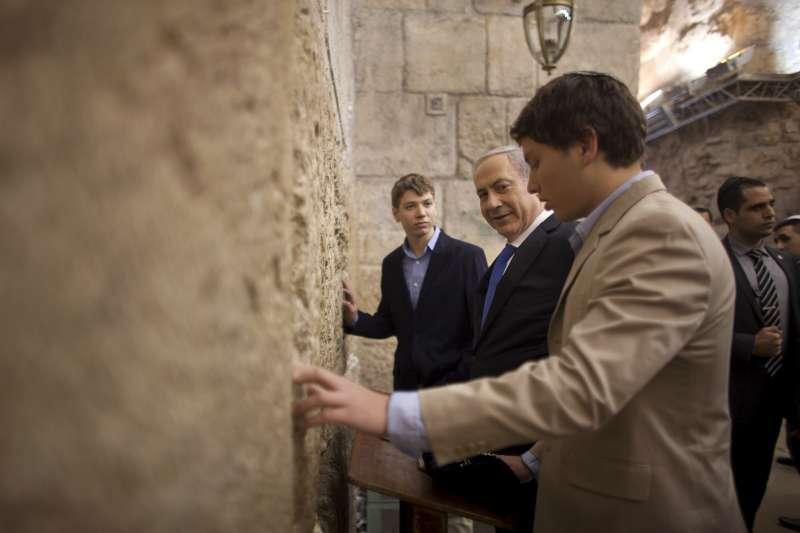 2013年1月,以色列總理納坦雅胡(中)帶著兩個兒子雅耶爾(左)與阿夫納到耶路撒冷的哭牆參拜(AP)