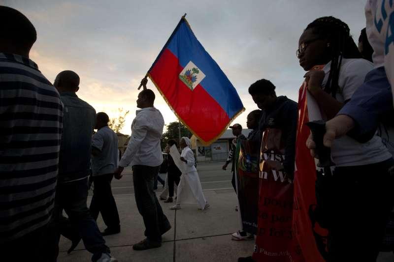 川普屎坑說:美國的海地移民高舉海地國旗(AP)