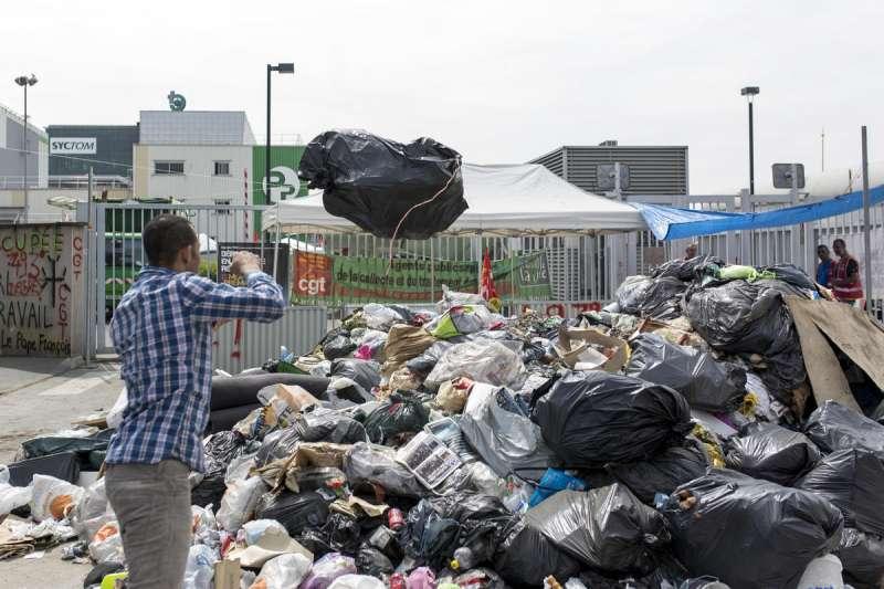 一名法國男子在巴黎附近的塞納河畔伊夫里丟垃圾。(美聯社)