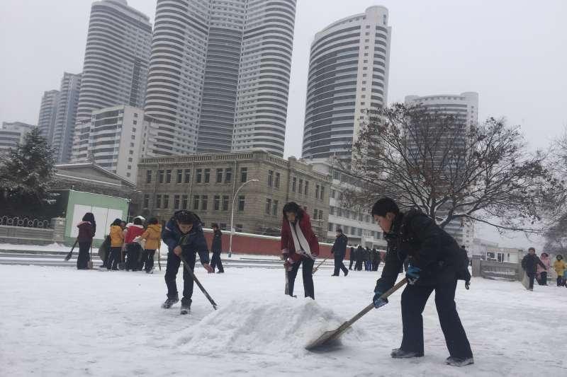 平壤民眾在街頭掃雪。(美聯社)
