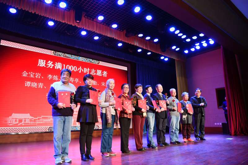 故宮志願者年終總結暨彙報展演會舉行,服務滿1000小時的志願者合影(新華社)