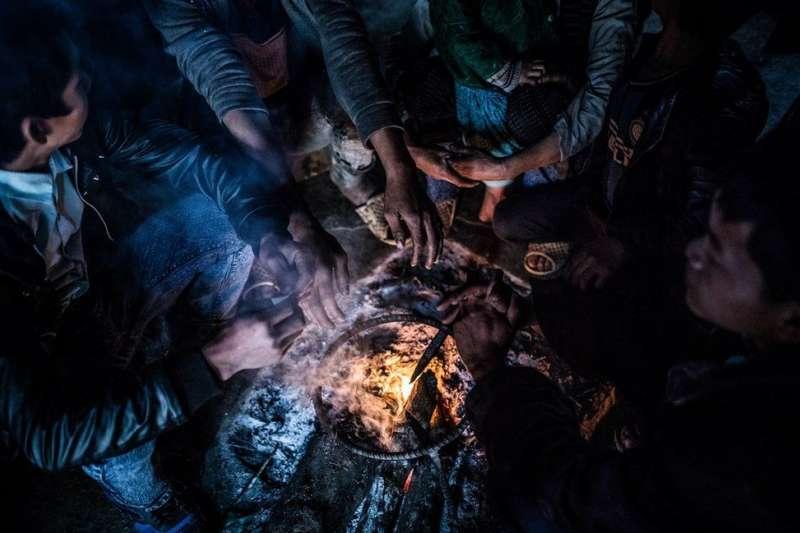 當地人圍坐在火盆周圍取暖。(BBC中文網)