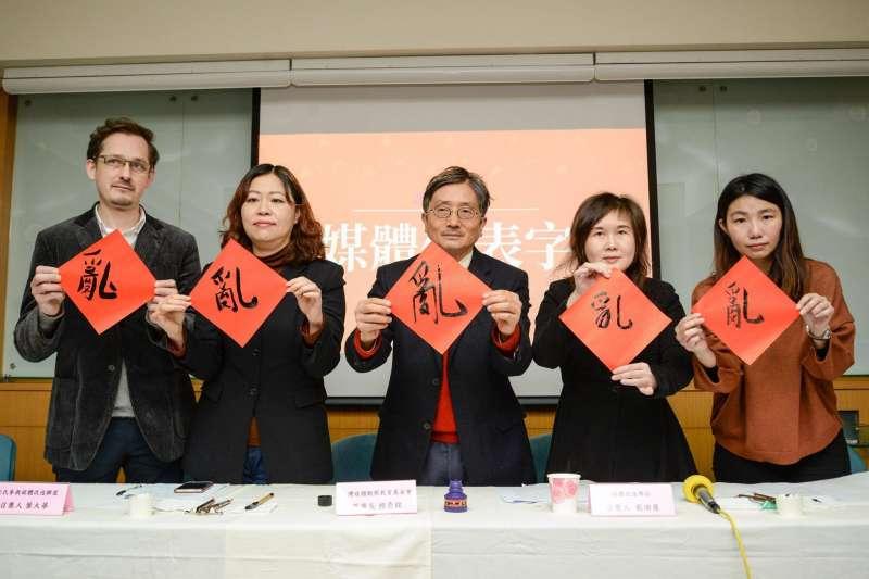 台灣媒體觀察教育基金會今(7)日發表媒體年度大事暨代表字票選結果,與會來賓一同揮毫寫下今年的年度媒體代表字「亂」。(台灣媒體觀察教育基金會提供)