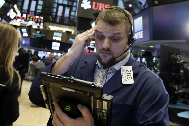 美股8日再度重挫超過千點,紐約證交所裡的交易員滿臉愁容。(美聯社)