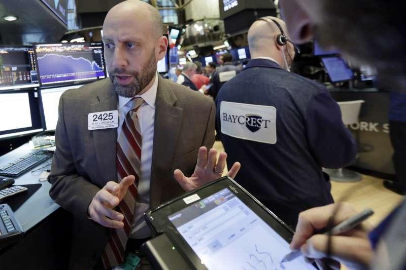 美股8日再度重挫超過千點,紐約證交所裡的交易員表情凝重。(美聯社)