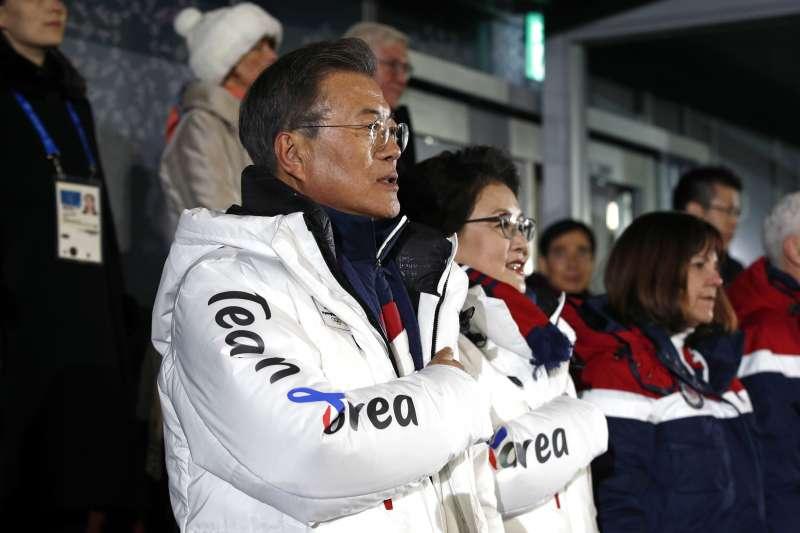 南韓總統文在寅與夫人金正淑身穿冬奧限量白色長羽絨衣。(美聯社)