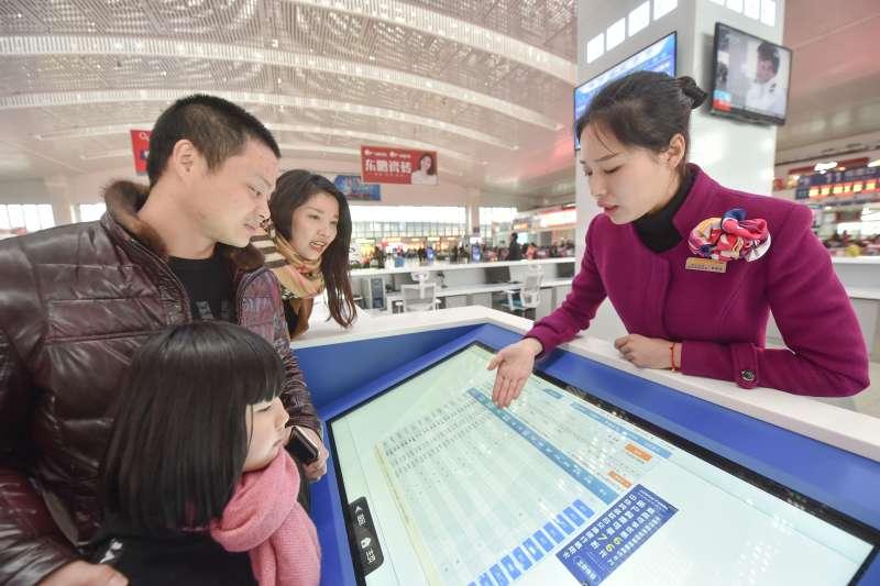 在福州火車站,工作人員爲旅客介紹剛剛投入使用的智能化自助服務系統。(新華社)