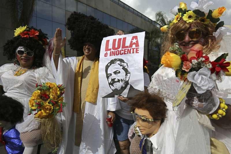 巴西首都巴西利亞11日的嘉年華上,前總統魯拉的支持者手持寫著「魯拉清白無罪」的標語(AP)