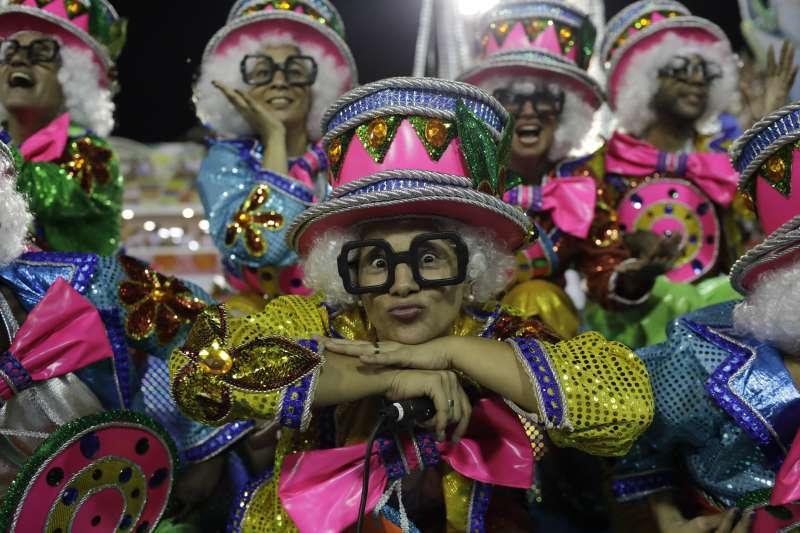 巴西里約熱內盧嘉年華熱鬧登場,12日凌晨仍有森巴舞學校的舞者表演(AP)
