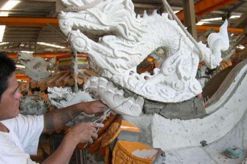 工人正在安裝廟宇上的配件。(BBC中文網)