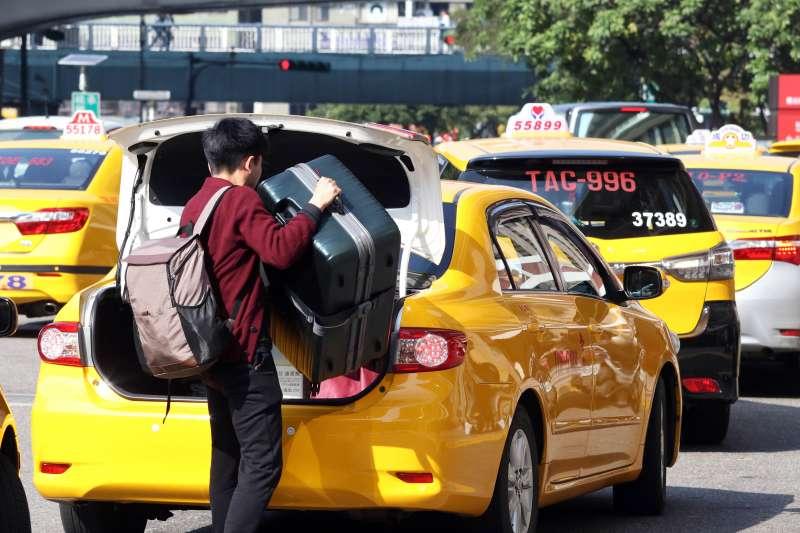 20180214-台北車站外,將行李箱從計程車裡搬出來的民眾。(蘇仲泓攝)