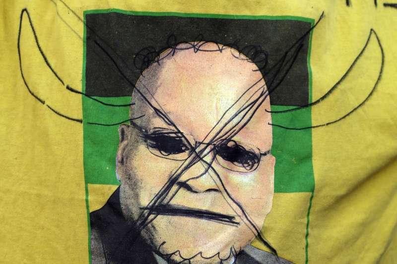 南非總統祖馬貪腐不斷,民眾在印有其肖像的衣服上寫下「小偷」。(美聯社)
