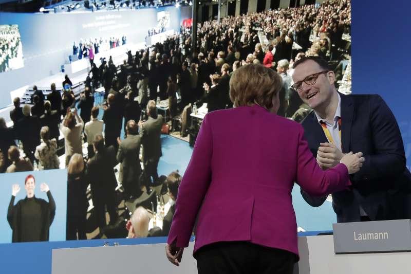 2月26日,德國基民盟在柏林舉行黨代表大會,史巴恩(右)與梅克爾握手致意(美聯社)