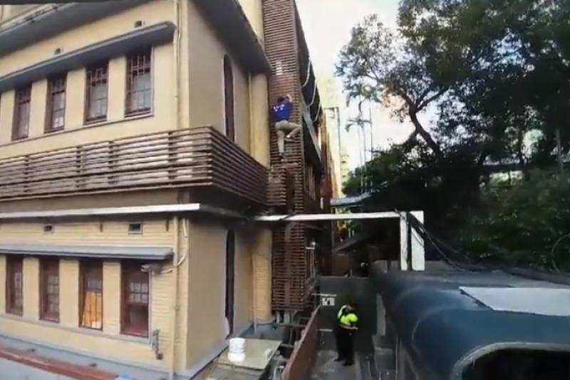 藍天行動聯盟秘書長繆德生原本打算爬牆進入立院,但在攀爬建物圍牆時,不慎摔落地面。(警政署提供)