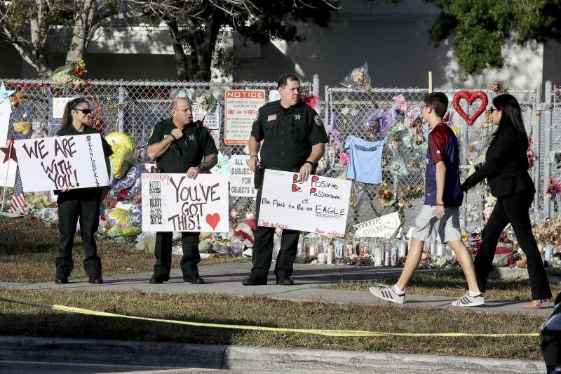 佛州槍擊案後的返校首日,學生們走過布滿鮮花和裝飾的街道。(AP)
