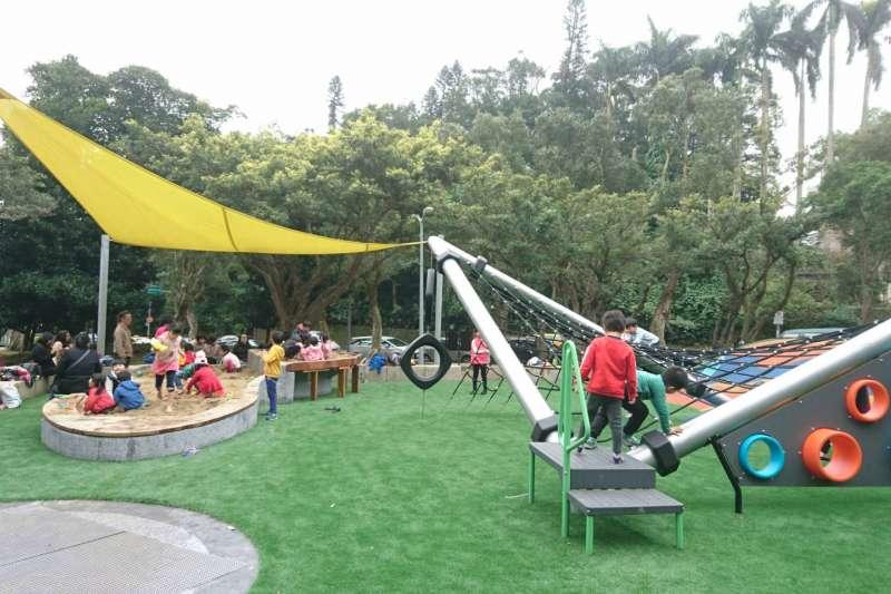 台北市政府推動「1區1共融」計畫,在文山區萬芳4號公園打造共融式遊戲場,一片綠油油仿真人工草皮地墊,與周遭樹木綠景和諧融為一體,吸引不少親子前往遊玩。(台北市政府提供)