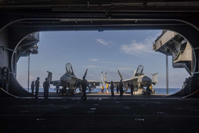 美軍卡爾文森號航空母艦在南海巡弋,兩架F/A-18F正準備從機庫上到甲板。(美國海軍官網)