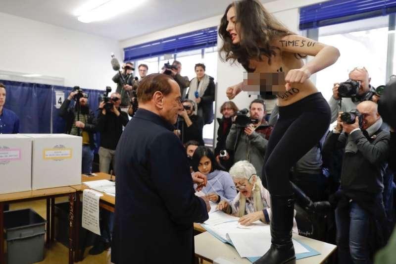 一名女性主義運動團體費曼(Femen)成員4日在投票所光著上身,當面向貝魯斯柯尼抗議。(美聯社)