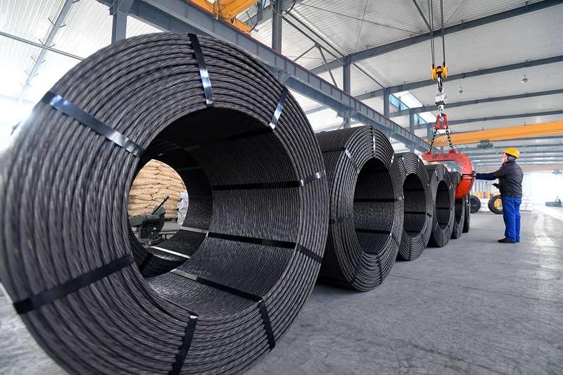 中國經濟,在河北省河間市寶澤龍金屬材料有限公司車間內,工人在吊運鋼絞線產品。(新華社)