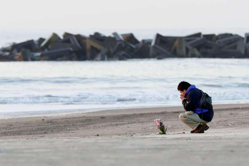一位東日本大地震的災民在福島海邊悼念因為海嘯逝去的親人。(AP)