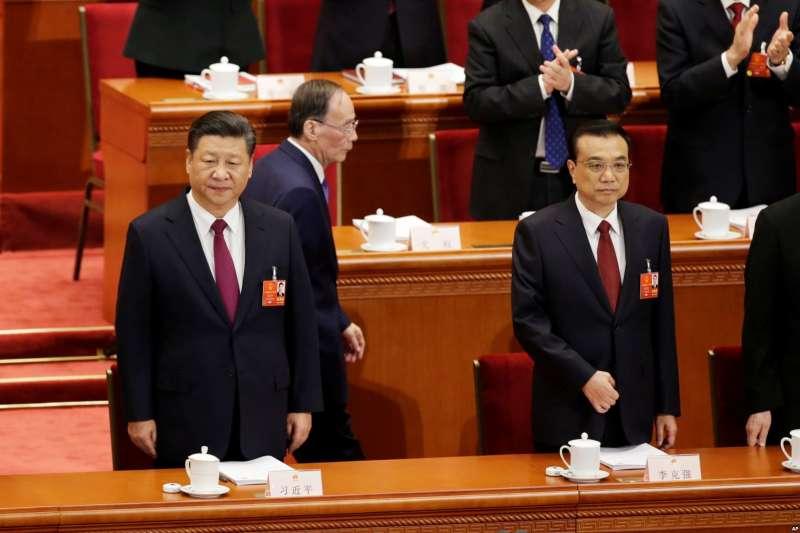 中國國家主席習近平和國務院總理李克強(前),曾經被西方媒體稱作中國反腐「沙皇」的人大主席團成員王岐山在他們身後走過。王岐山又回來了。南華早報3月5日引用消息人士的話說,王岐山將成為國家副主席,在未來五年致力於解決中國與美國的外交和貿易關係問題。(美國之音)
